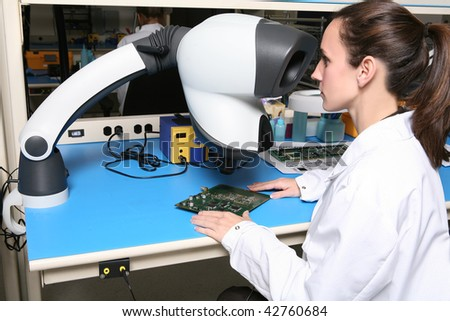 A pretty woman computer technician examining a printed circuit board with a microscope - stock photo