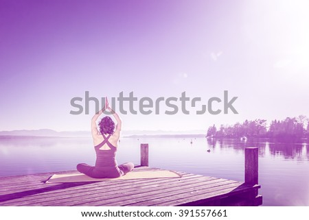 A pretty woman doing yoga at the lake