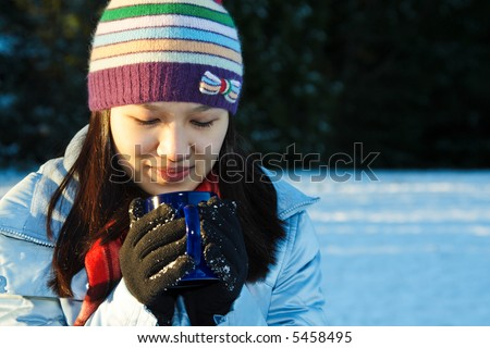 A pretty woman drinking a cup of coffee outdoor