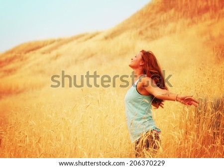 a pretty woman enjoying summer outside toned with a retro vintage instagram filter  - stock photo