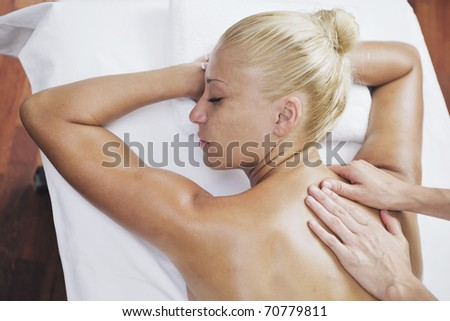 A pretty woman getting a shoulder and back massage at spa and wellness center - stock photo