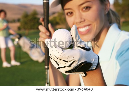 A pretty woman golfer holding a golf ball - stock photo
