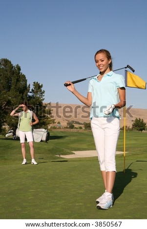 A pretty woman golfer on the putting green - stock photo