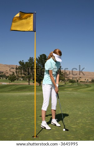 A pretty woman golfer putting for par on the gold course - stock photo