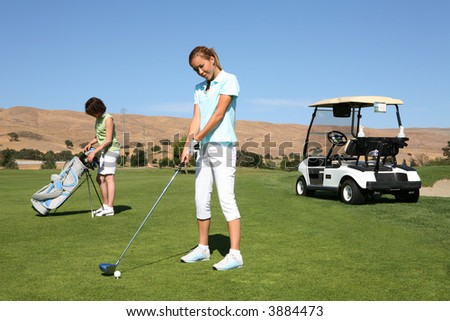 A pretty woman golfer ready to begin the golf course - stock photo