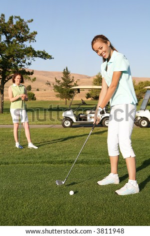 A pretty woman golfer ready to hit on the fairway - stock photo