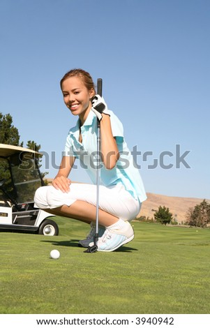 A pretty woman golfer ready to putt the ball in the hole - stock photo