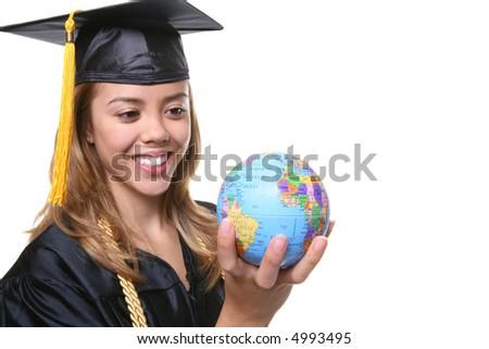 A pretty woman graduate holding a small globe - stock photo