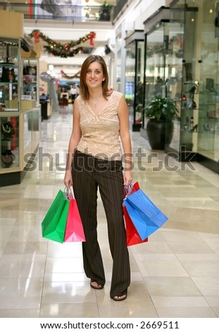 A pretty woman holding bags in the shopping mall - stock photo