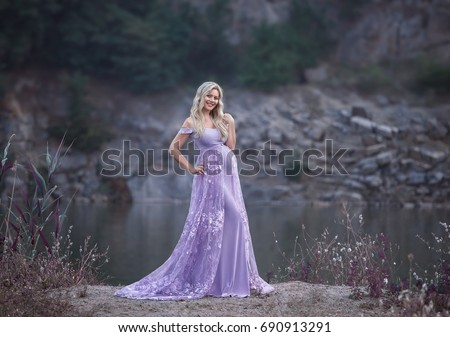 A pretty woman in a beautiful, purple dress with a long train. Fantastic picture of pregnancy. Creative colors.