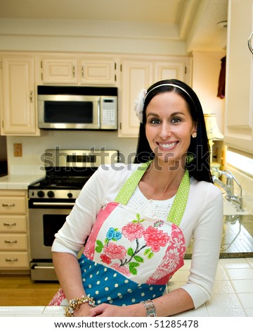 A pretty woman in a clean, modern, kitchen, leaning on the counter and smiling. - stock photo