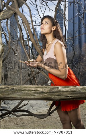 A pretty woman is holding an egg nest and hopefully looking up. The background is small woods, vine tree and high building skyline/Looking for Home