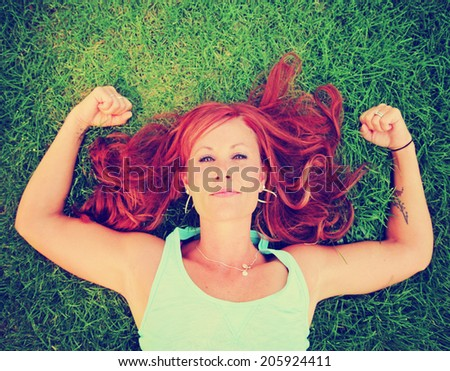a pretty woman lying in green grass toned with a retro vintage instagram filter  - stock photo