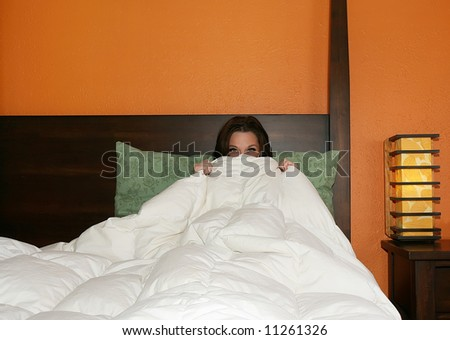 a pretty woman peeking out of the covers - stock photo