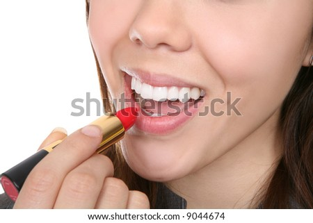 A pretty woman putting on her make-up lipstick