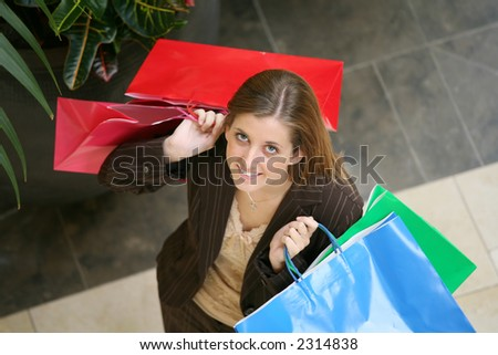 A pretty woman shopping carrying colorful bags - stock photo