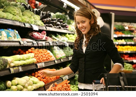 A pretty woman shopping for vegetables in the supermarket - stock photo