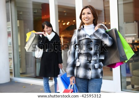 A pretty woman shopping with colorful bags walking to the next store - stock photo