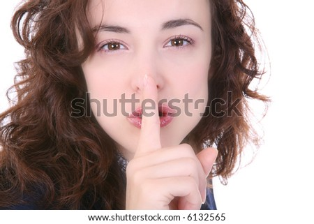 A pretty woman signaling for silence with her finger - stock photo