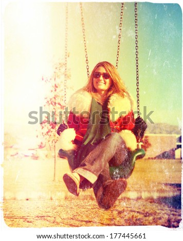 a pretty woman sitting in a swing done with a retro vintage instagram filter  - stock photo