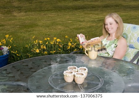 A pretty woman sitting on a patio drinking coffee and reading a book - stock photo