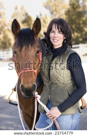 A pretty woman standing beside her pretty bay horse after an afternoon ride. - stock photo