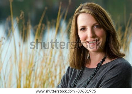 A pretty woman standing outside at a quiet country lake. - stock photo