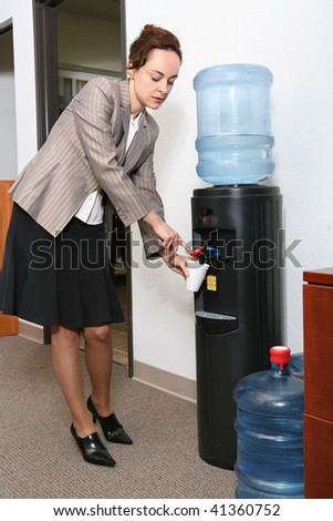 A pretty woman taking a water break in the office - stock photo