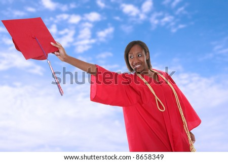 A pretty woman tossing her cap at graduation - stock photo