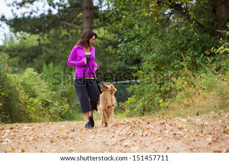 A pretty woman walking her dog - stock photo