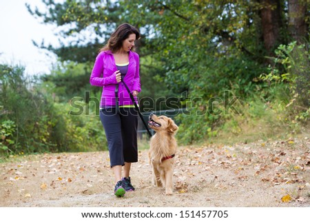 A pretty woman walking her dog on a trail