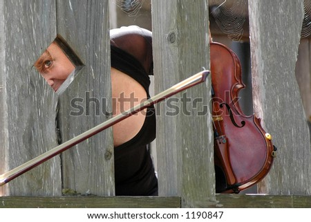 "A pretty woman with a great smile and a matching sense of humor ""poses"" with her violin in a park. - stock photo"