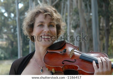 A pretty woman with a great smile poses with her violin in a park.