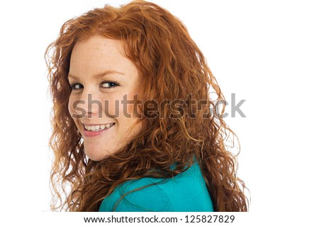 A pretty woman with red hair looking back over her shoulder. - stock photo