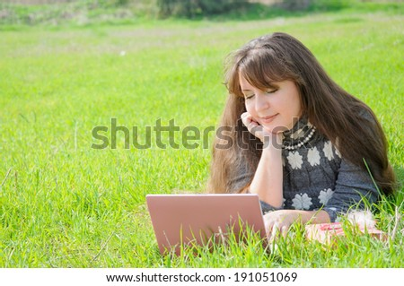 A pretty women working on laptop computer on green grass in the park - stock photo