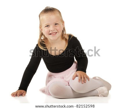 A pretty 3-year-old sitting pretty in her ballerina clothes.  Isolated on white. - stock photo