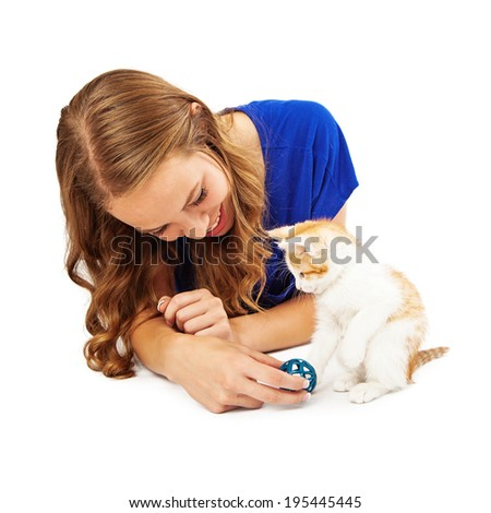 A pretty young adult female volunteer at an animal shelter playing with a little kitten - stock photo