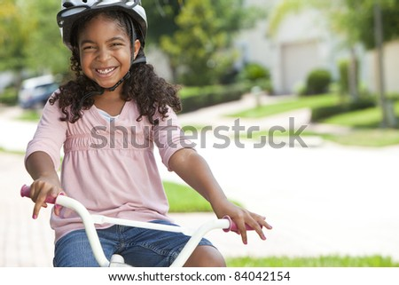 A pretty young African American girl with a big smile riding her bicycle outside - stock photo
