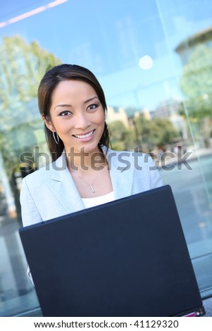 A pretty, young  asian business woman at office building - stock photo