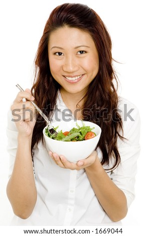 A pretty young asian woman in a white blouse is eating a salad in a bowl