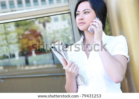 A pretty young asian woman on the phone at office building