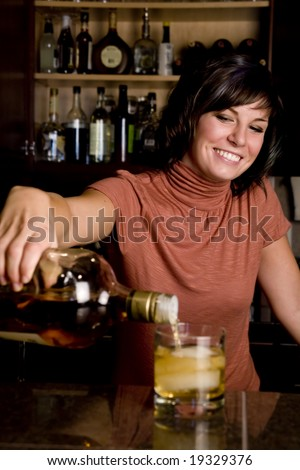 A pretty young bartender pouring a cold drink - stock photo
