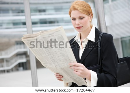 A pretty, young business woman at office building reading newspaper - stock photo