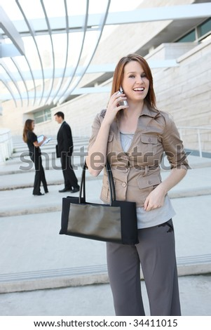 A pretty young business woman at the office building on phone