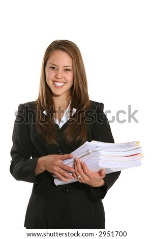 A pretty young business woman carrying a stack of folders