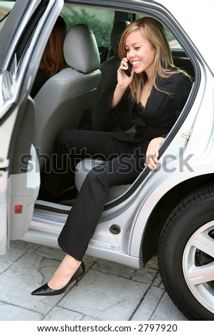 A pretty young business woman getting out of a car - stock photo