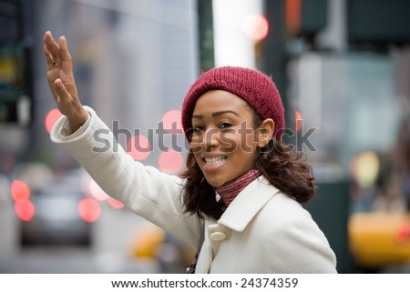A pretty young business woman hails a taxi cab in the city. - stock photo