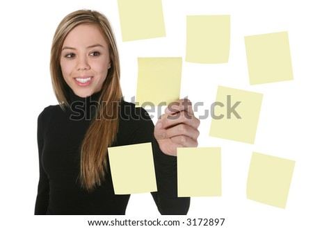 A pretty young business woman taking a note off the board - stock photo