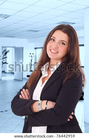 A pretty young businesswoman smiling in her office. Blue toned background. - stock photo