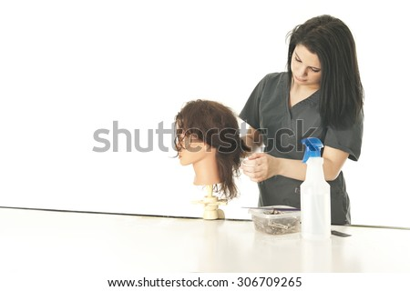 A pretty young cosmetology student studying her practice mannequin's hair as she begins to style it.  On a white background with space on the left for your text. - stock photo